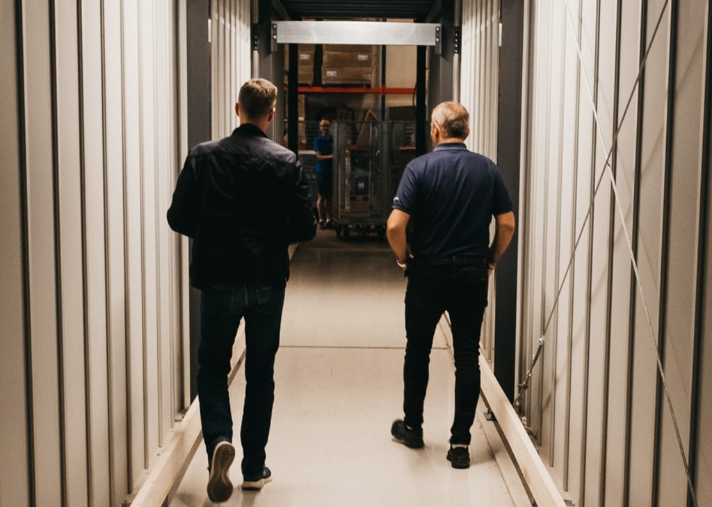 GS Bildeler co-founder, Trond Gule, and Element Logic Sales Manager, Øyvind Kollerud, walks through the custom-made tunnel through the AutoStore-system in the Oslo-warehouse.