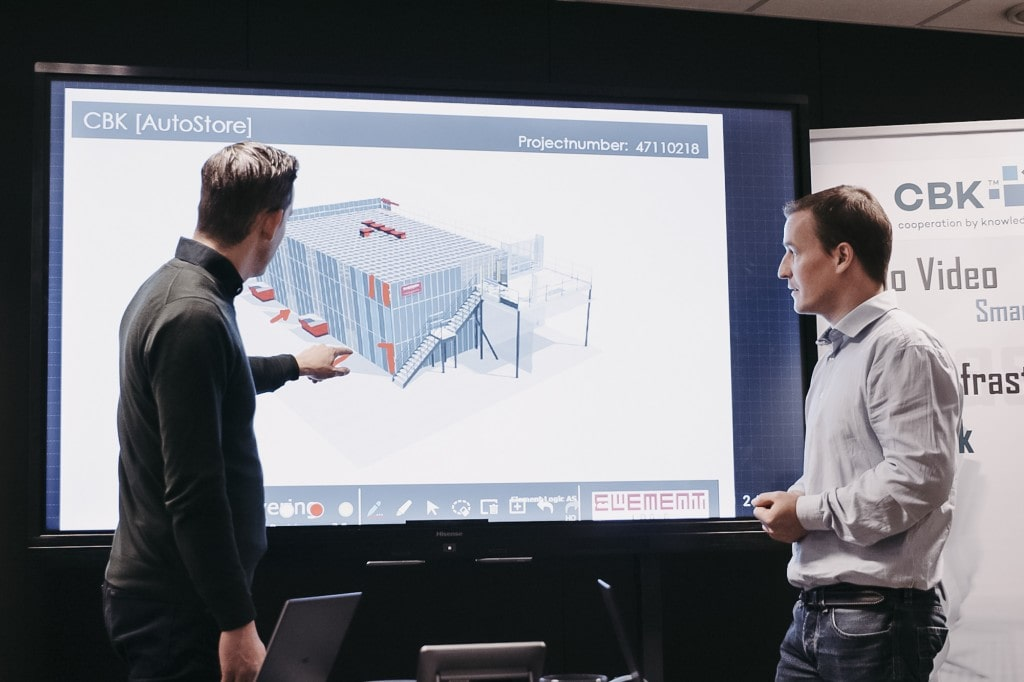 Two men are pointing and looking at a presentation of a drawing of an AutoStore solution.