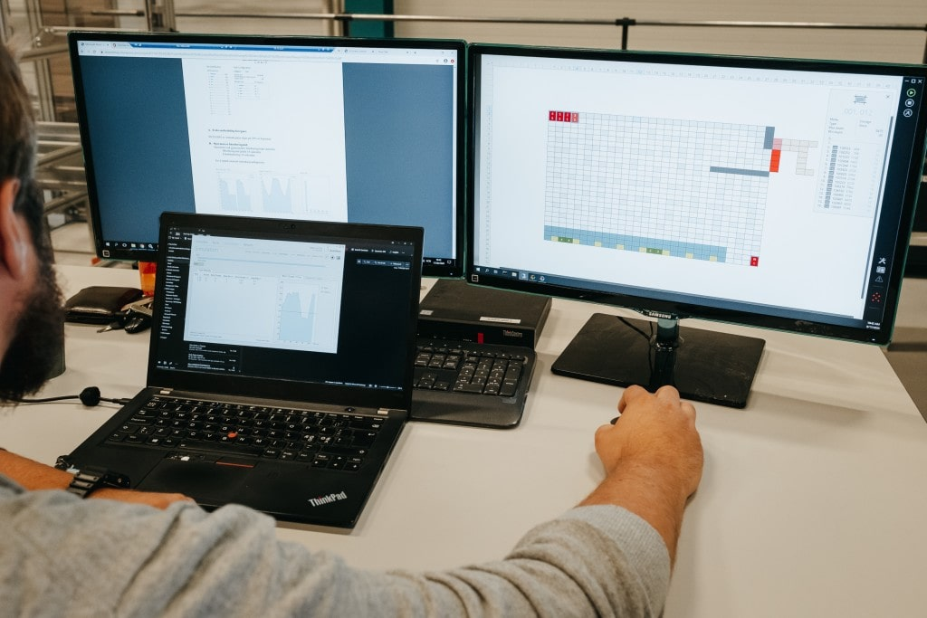 A man is working on the AutoStore solution with three computer screens.