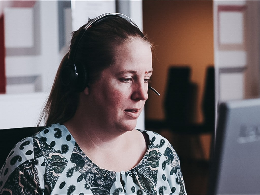 A close-up of a woman talking in headphones in front of a computer.