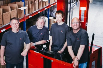 Four Colliflow employees stand in the warehouse and smile at the camera.